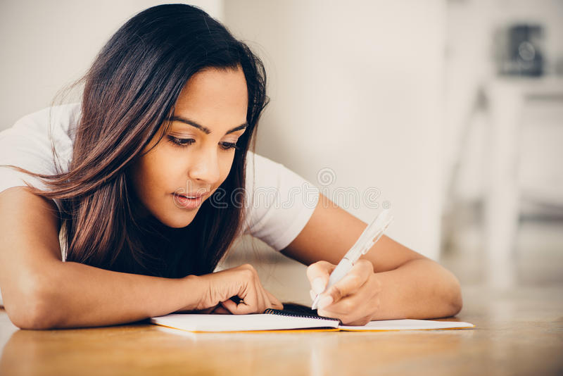 Étude indienne heureuse d'écriture d'éducation d'étudiante photo stock