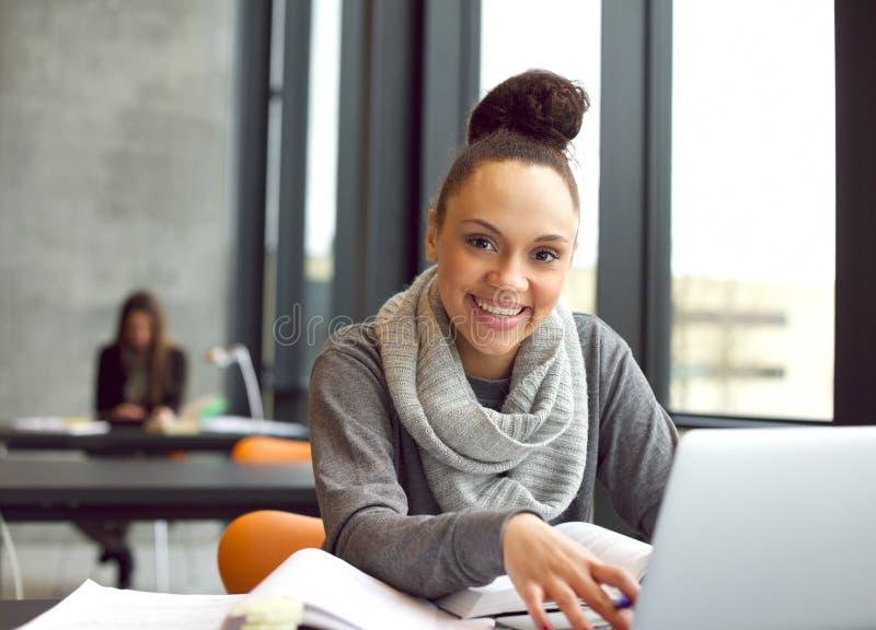 Études heureuses de jeune femme dans la bibliothèque images libres de droits