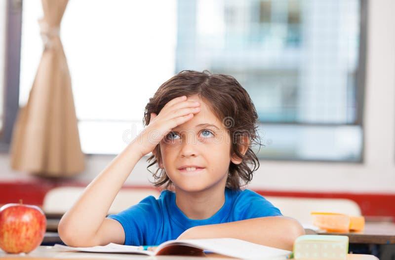 Étudiant à l'école primaire pensant à la résolution des problèmes photographie stock