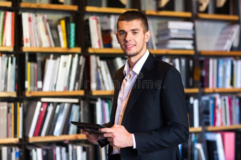 étudiant à l'aide d'un comprimé dans la bibliothèque l'étudiant se tient avec le comprimé dans des ses mains dans une bibliothèqu photo libre de droits
