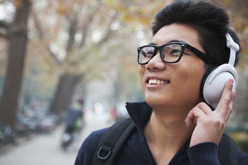 Étudiant écoutant la musique sur le campus d'université image stock