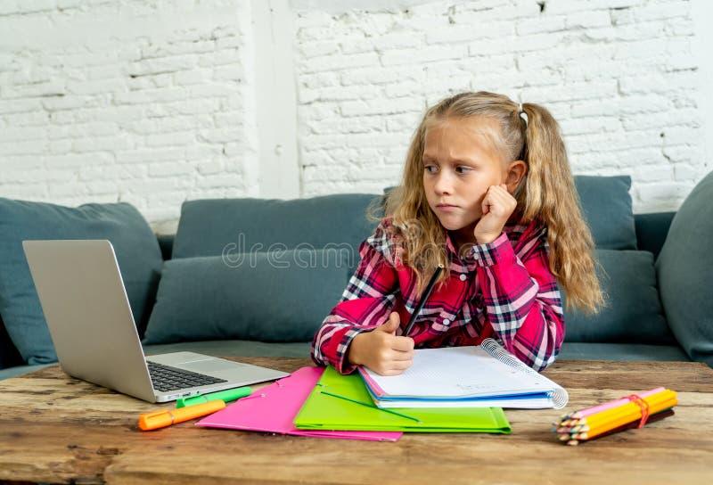 Étudiant élémentaire mignon se sentant triste et embrouillant tout en faisant la tâche difficile avec son ordinateur portable à l images libres de droits