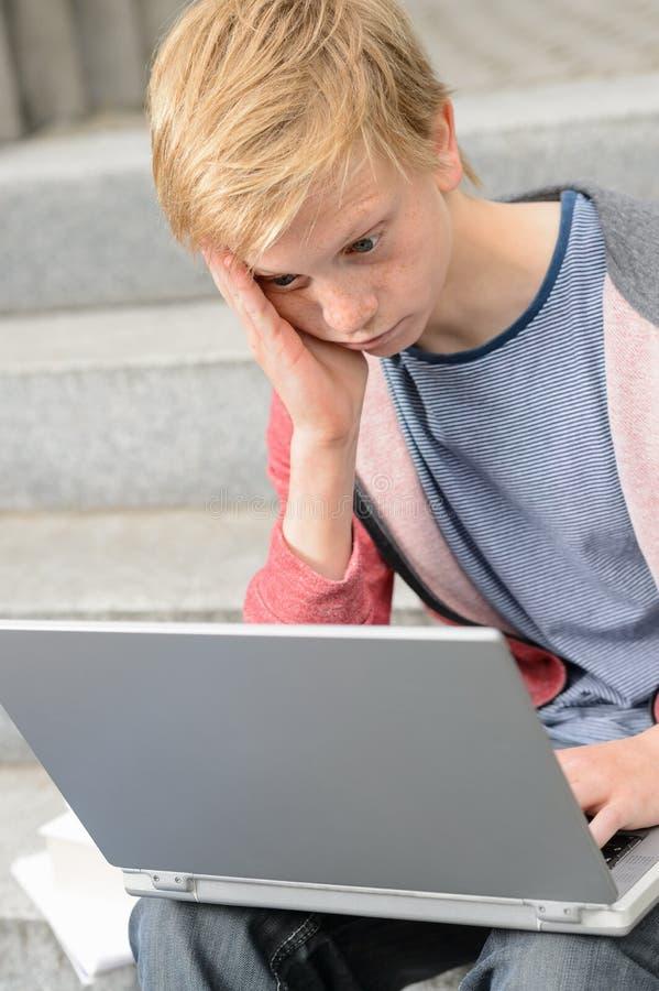 Étudiant adolescent ennuyé à l'aide de l'ordinateur portable photographie stock libre de droits