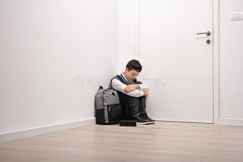 Étudiant adolescent triste assis dans un coin photo libre de droits