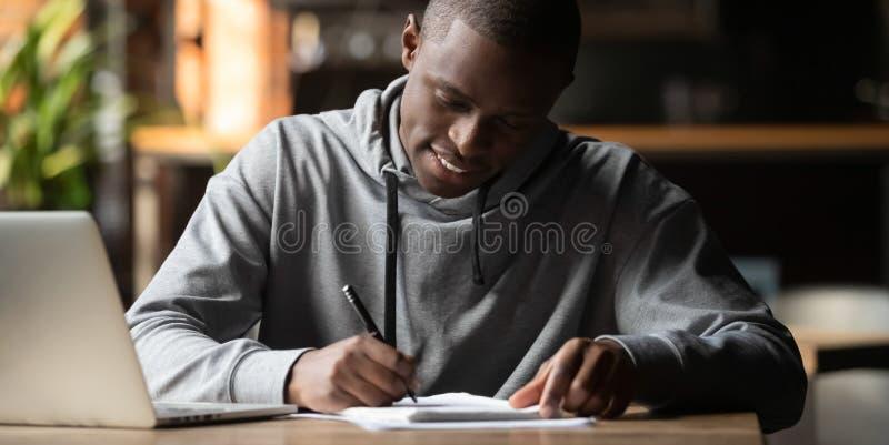 Étudiant africain focalisé s'asseyant à l'intérieur pour écrire sur le carnet photos libres de droits