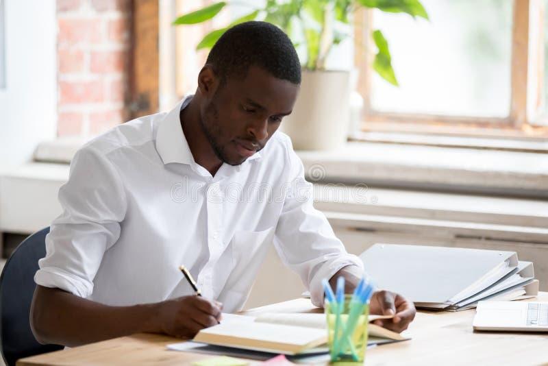 Étudiant africain sérieux d'homme étudiant le manuel de lecture faisant des notes photo stock