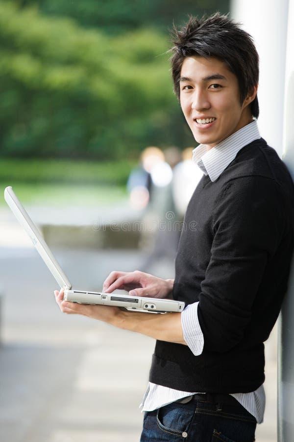 Étudiant asiatique avec l'ordinateur portatif images stock