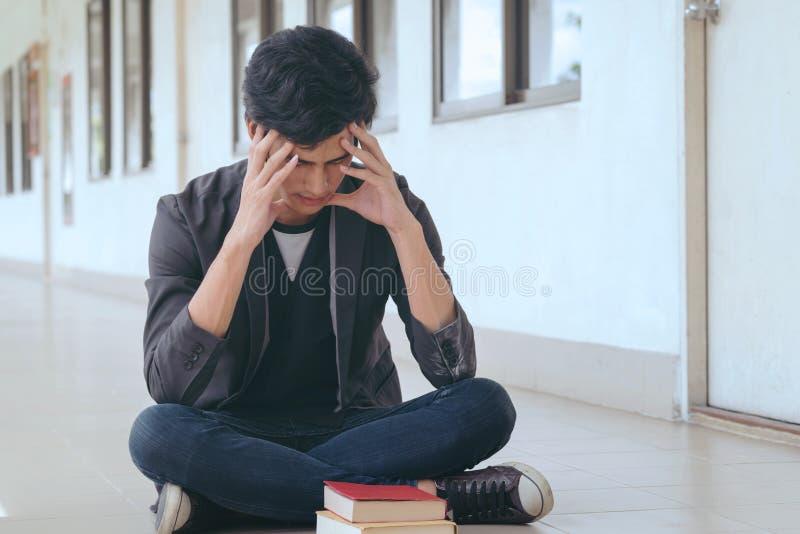 Étudiant asiatique s'asseyant sur la pièce avant, frustrée sur son travail et images stock