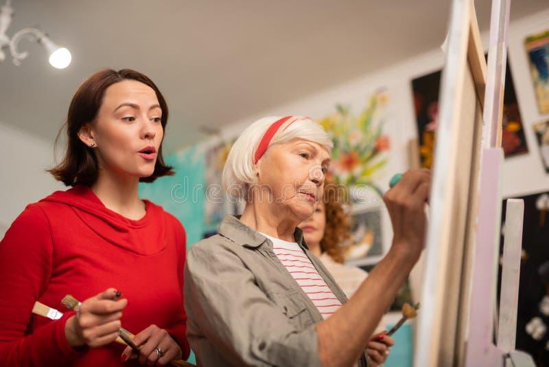 étudiant aux cheveux foncés observant sa peinture âgée de professeur photographie stock libre de droits