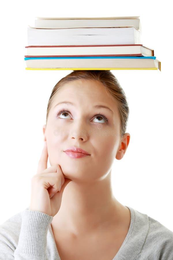 Étudiant avec des livres sur sa tête photos stock