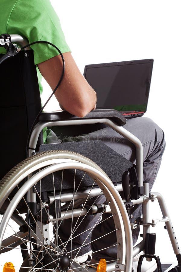 Étudiant avec l'ordinateur portable sur le fauteuil roulant photo libre de droits