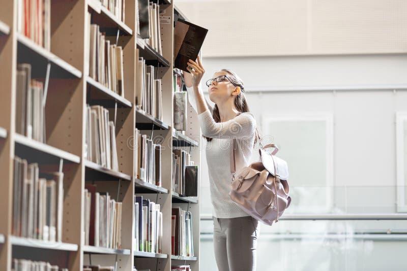 Étudiant choisissant le livre à la bibliothèque universitaire photos libres de droits