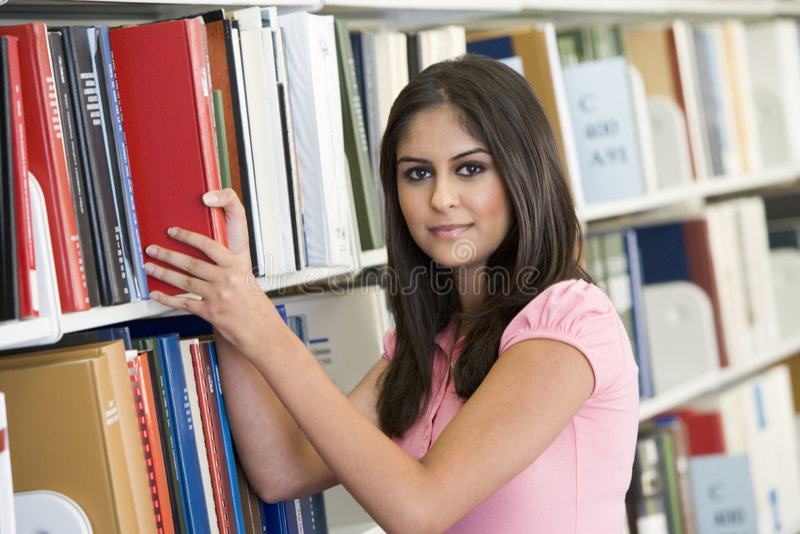 Étudiant choisissant le livre à partir de la bibliothèque photos libres de droits
