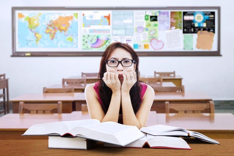 Étudiant confus de brune avec des livres dans la classe photos libres de droits