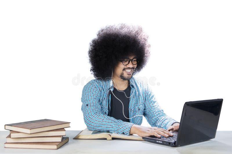 Étudiant crépu à l'aide d'un ordinateur portable et d'un casque sur le studio photo stock