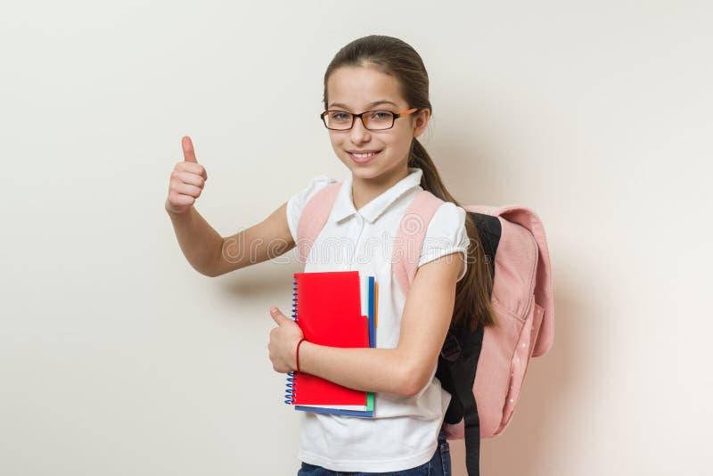 Étudiant d'école de fille, avec un sac à dos et des carnets montrant des pouces vers le haut de signe, mur lumineux de fond à l'é image stock