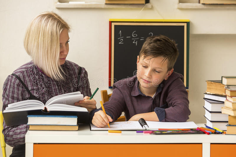 Étudiant d'école primaire faisant des devoirs avec un tuteur aide photographie stock libre de droits