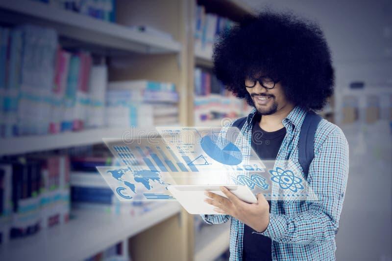 Étudiant d'Afro à l'aide du comprimé dans la bibliothèque photo libre de droits