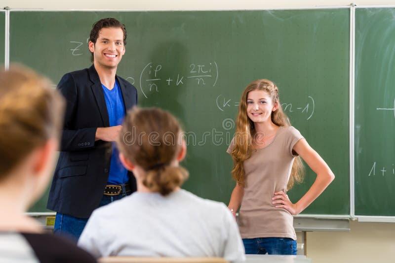 Étudiant d'essai de professeur dans des leçons de maths dans la classe d'école photo libre de droits