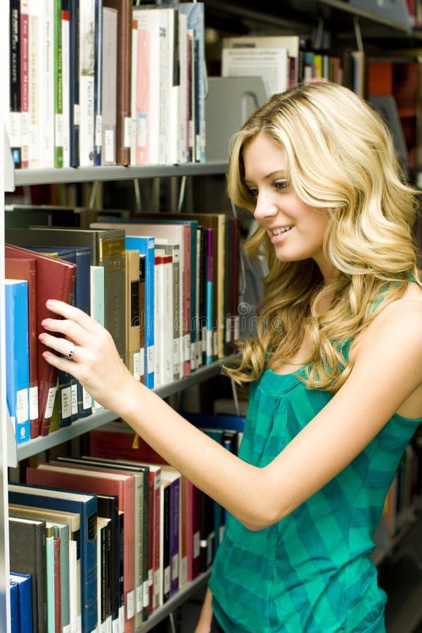 Étudiant dans la bibliothèque photo libre de droits