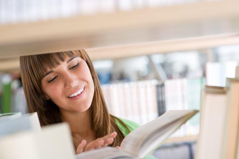 Étudiant dans la bibliothèque - la femme gaie a affiché le livre images stock