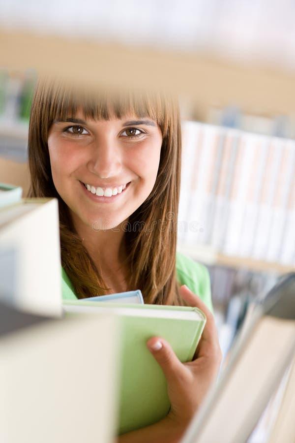 Étudiant dans la bibliothèque - livre gai de prise de femme photo stock