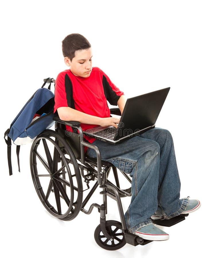 Étudiant dans le fauteuil roulant avec l'ordinateur portatif photographie stock libre de droits