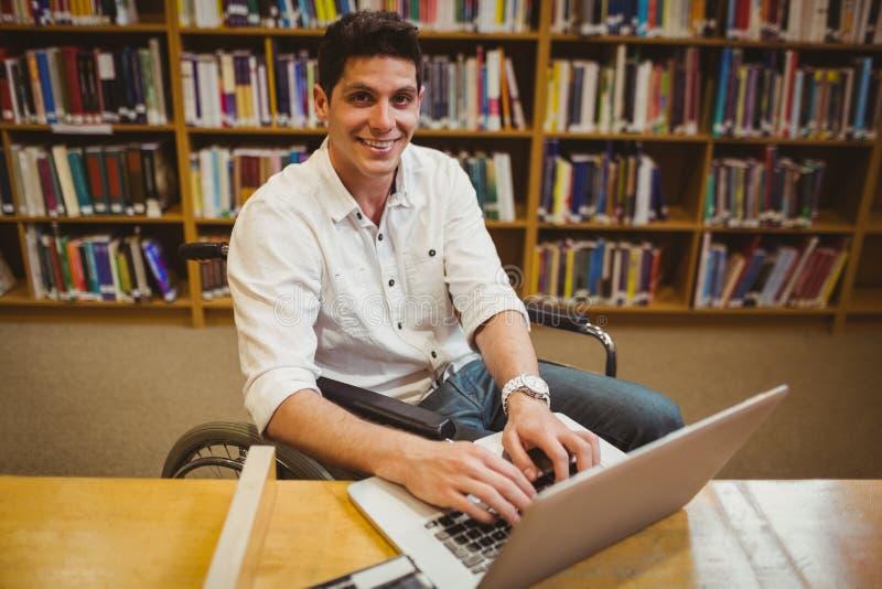 Étudiant dans le fauteuil roulant dactylographiant sur son ordinateur portable photographie stock