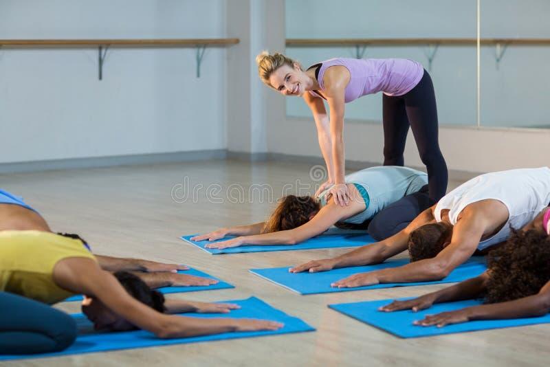 Étudiant de aide d'instructeur de yoga avec une pose correcte images libres de droits