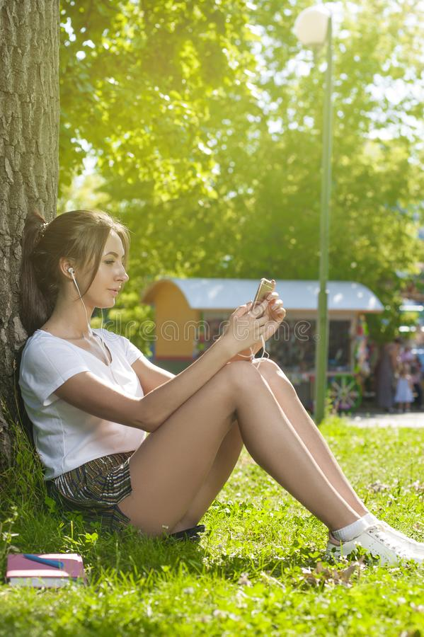 Étudiant de charme Girl Sitting sur l'herbe verte photo stock