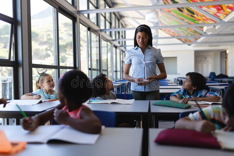 Étudiant de enseignement de professeur féminin au bureau dans la salle de classe photo libre de droits