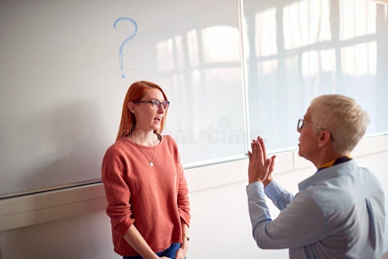 Étudiant de explication et de interrogation de professeur dans la salle de classe à bord photos stock