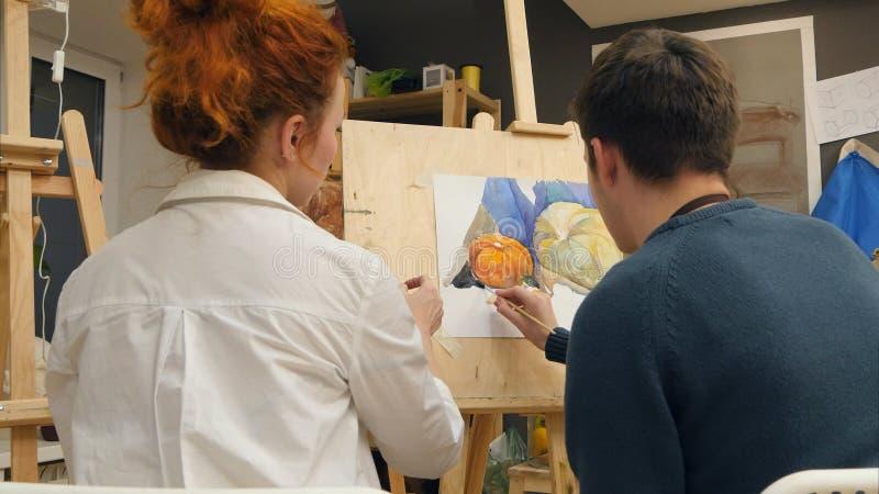 Étudiant de explication féminin de professeur d'art comment appliquer des aquarelles photographie stock libre de droits