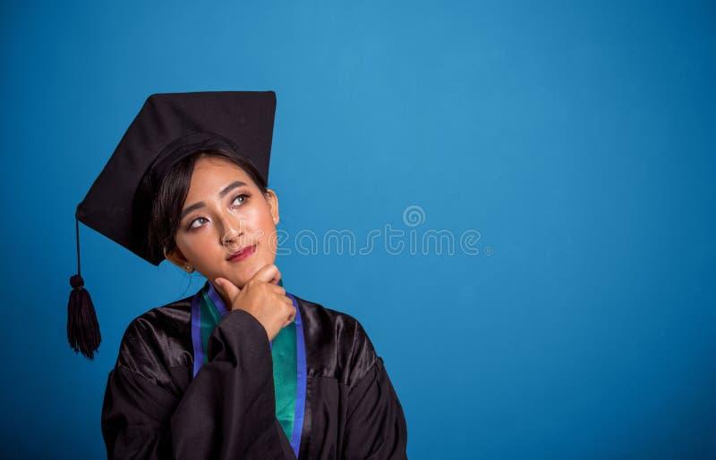 Étudiant de graduation réfléchi, au-dessus de bannière bleue photographie stock