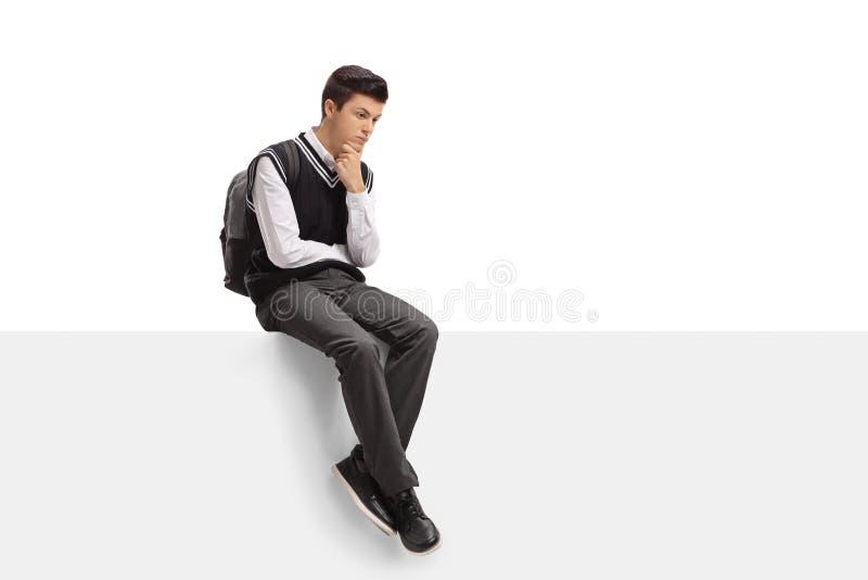 Étudiant de l'adolescence songeur assis sur un panneau image libre de droits