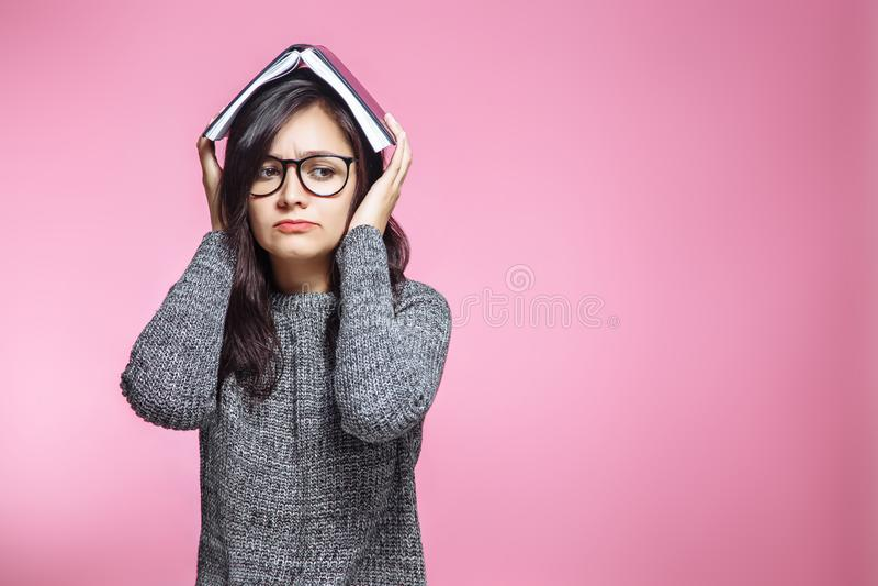 Étudiant de l'adolescence triste avec le livre sur la tête sur le fond rose image libre de droits