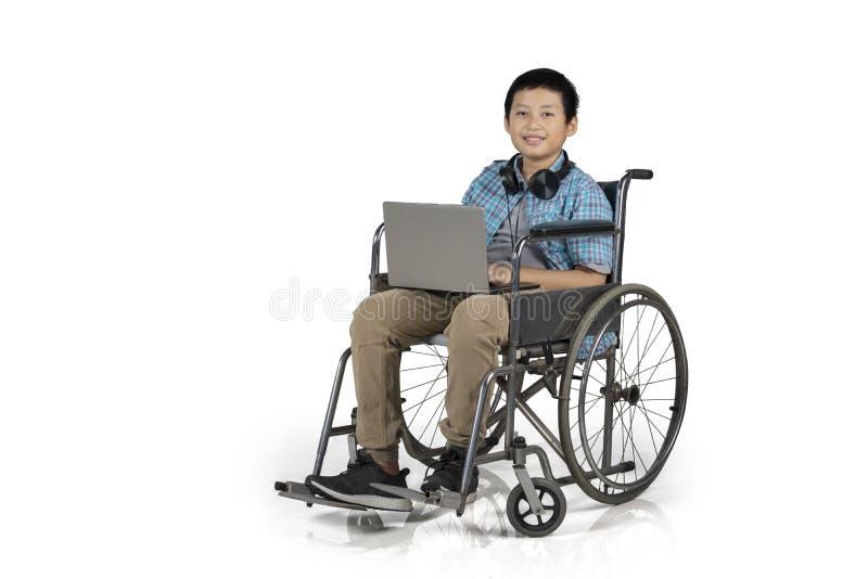 Étudiant de la préadolescence avec l'ordinateur portable dans un fauteuil roulant images libres de droits