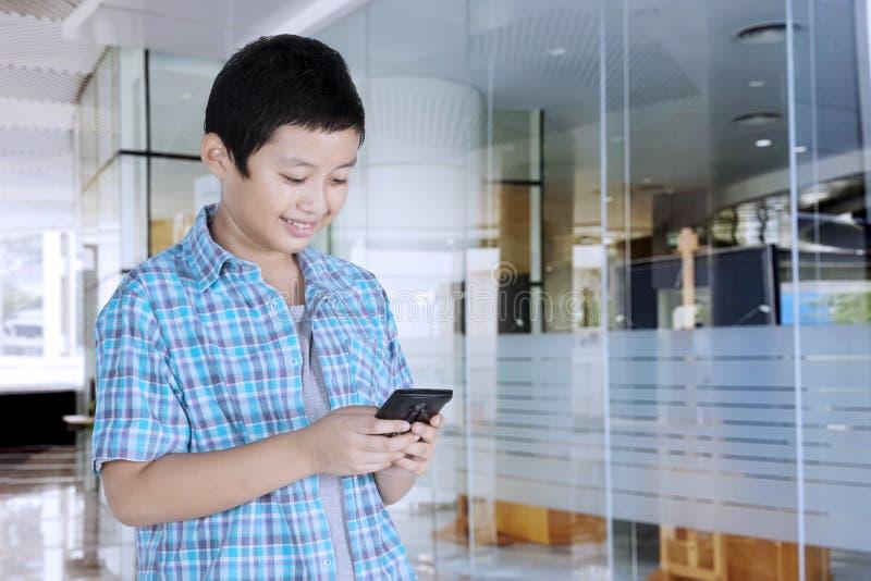 Étudiant de la préadolescence bel à l'aide d'un smartphone image libre de droits
