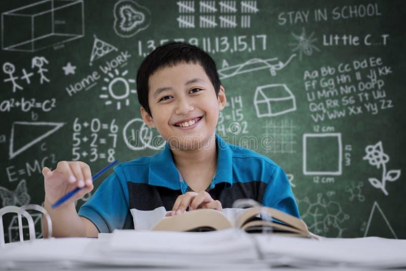 Étudiant de la préadolescence de garçon faisant un examen dans la salle de classe image stock
