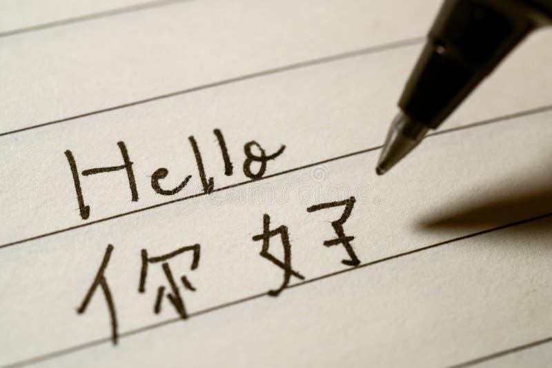 Étudiant de langue chinoise de débutant écrivant le mot de bonjour dans le macro tir de caractères chinois image stock