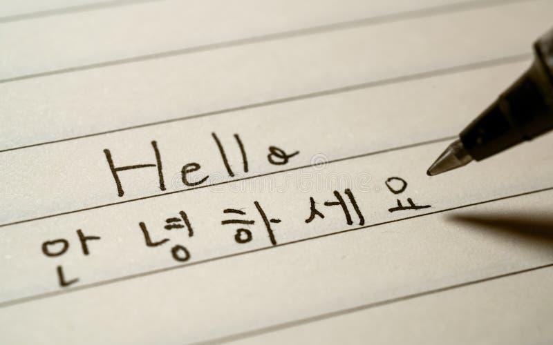 Étudiant de langue coréen de débutant écrivant le mot Annyeonghaseyo de bonjour en caractères coréens sur un carnet photographie stock libre de droits