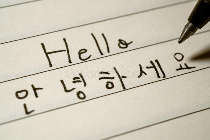 Étudiant de langue coréen de débutant écrivant le mot de bonjour dans le macro tir de caractères coréens photographie stock