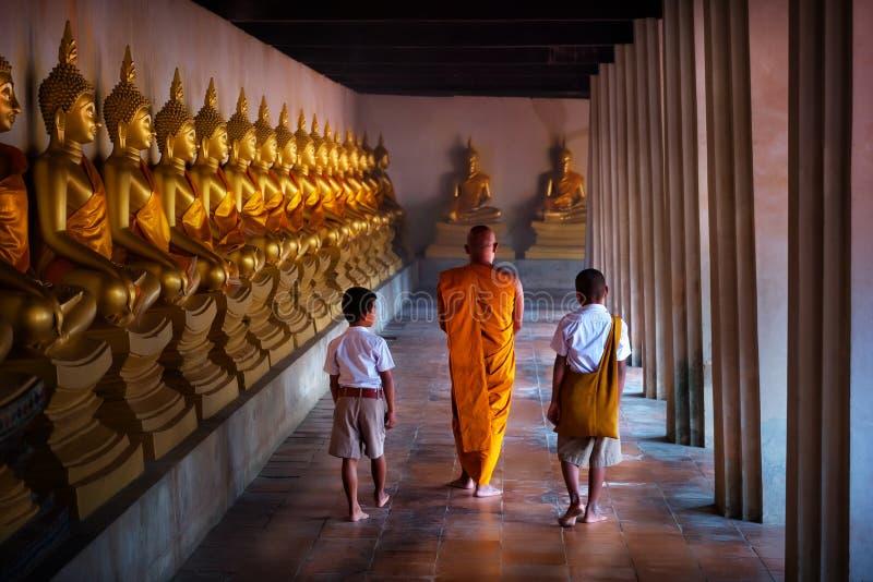 Étudiant de moine et de garçon de remorquage à la statue d'or de Bouddha, jour de Makhabucha image stock