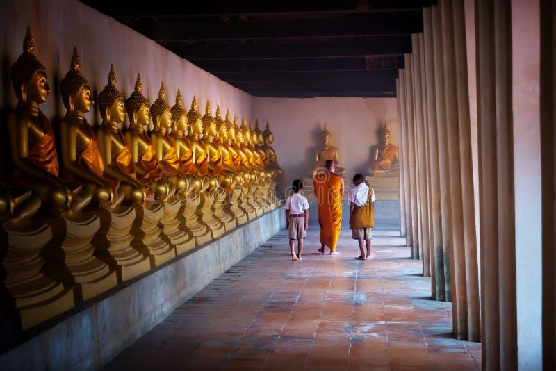 Étudiant de moine et de garçon de remorquage à la statue d'or de Bouddha, jour de Makhabucha image libre de droits