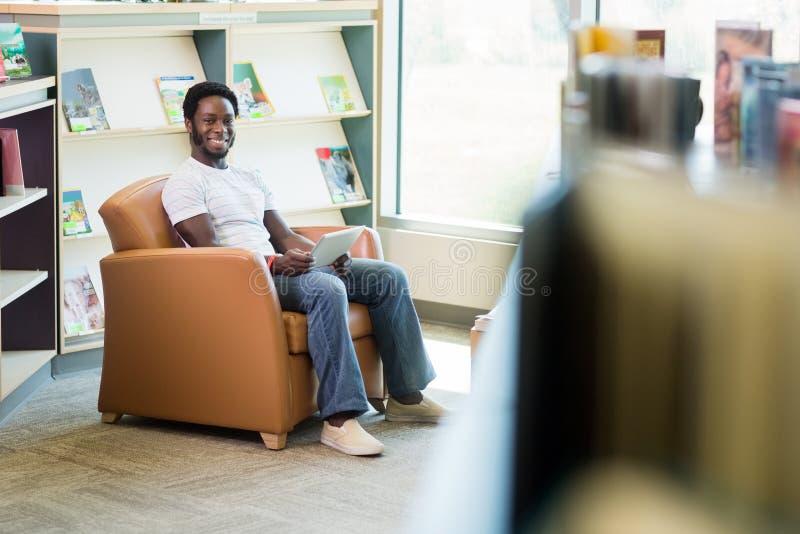 Étudiant de sourire With Digital Tablet dans la bibliothèque image libre de droits