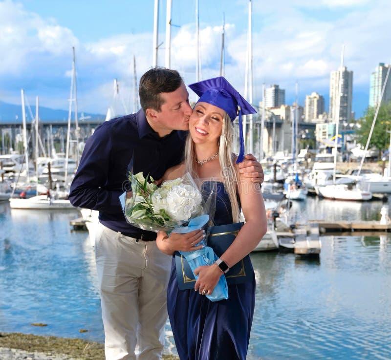 Étudiant de troisième cycle dans la robe scolaire avec les fleurs et le diplôme recevant des étreintes et des baisers de l'ami ap photos libres de droits
