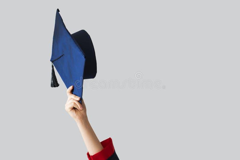 Étudiant de troisième cycle se levant vers le haut de son chapeau photo stock