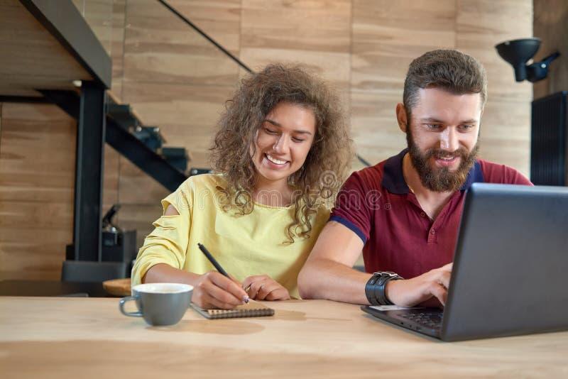 Étudiant des étudiants s'asseyant en café confortable, utilisant l'ordinateur portable photo stock