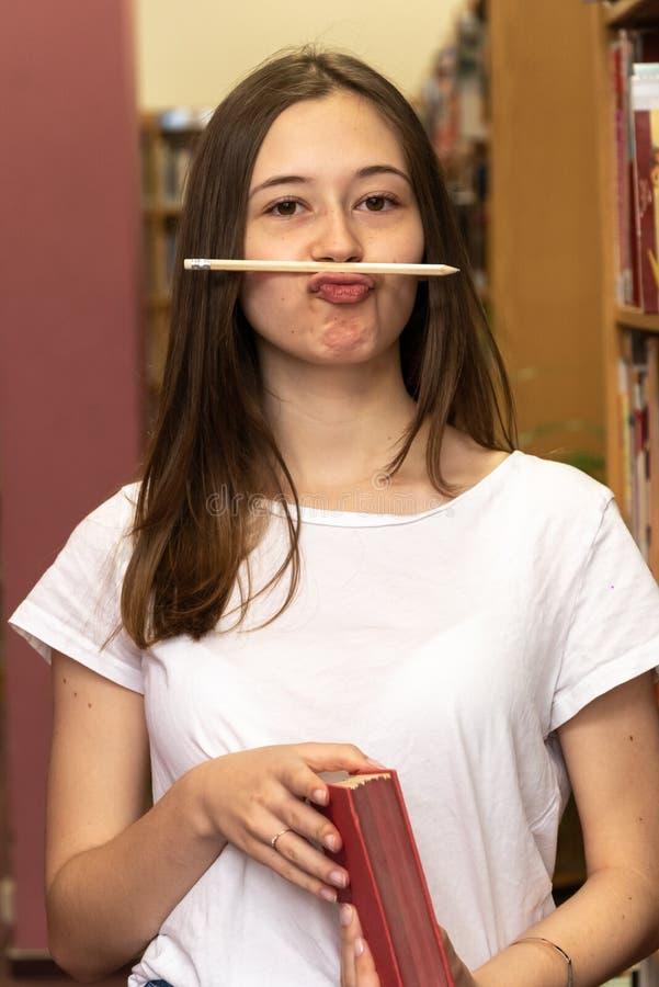 Étudiant drôle jouant avec son crayon photographie stock