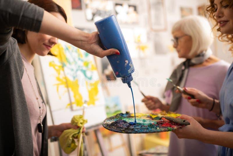 étudiant en art aux cheveux foncés versant la gouache bleue sur la palette de couleurs photos libres de droits